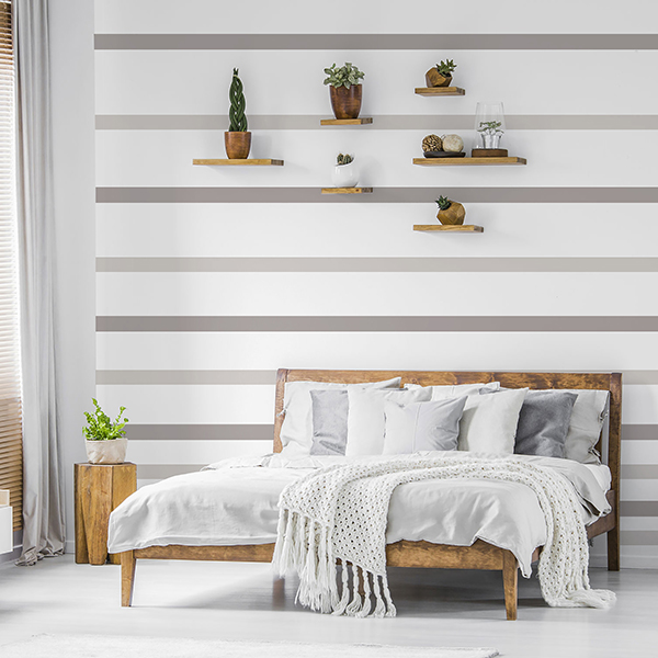 Wooden shelves with plants above a comfortable double bed in a s