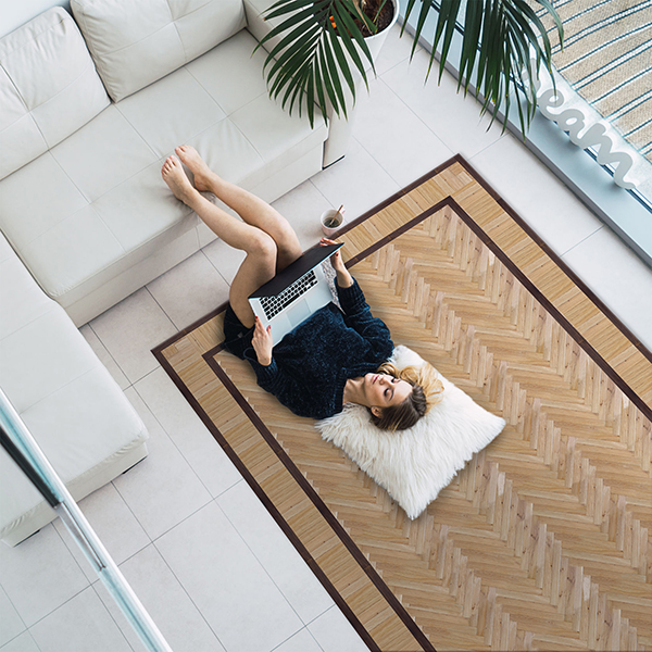 Overhead view of woman cuddling on floor with legs on couch and